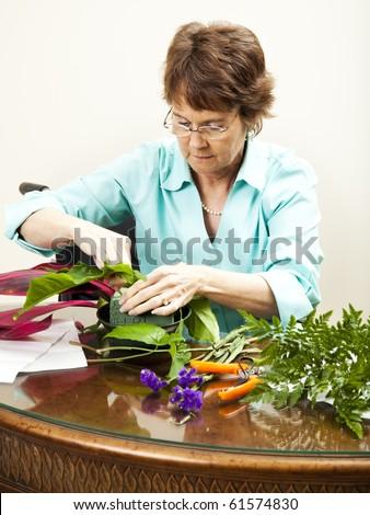 Disabled florist in wheelchair, creating a flower arrangement.