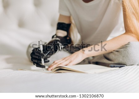 disabled girl learning to write with a prosthetic arm. close eup cropped photo. writing process