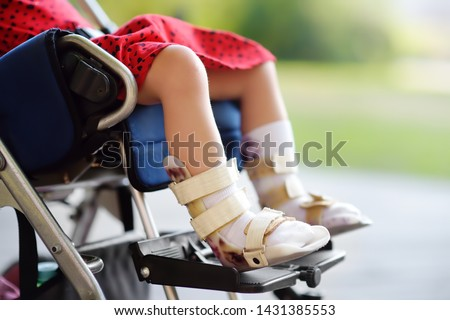 Disabled girl sitting in wheelchair. On her legs orthosis. Child cerebral palsy. Inclusion. Family with disabled kid. Stock photo ©