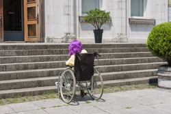 Disabled girl with purple hair in a wheelchair  in front of a stair