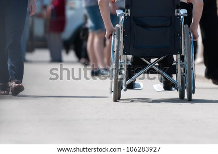 Disabled (handicapped) person on wheeled chair among people without disabilities. Place for copy.
