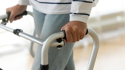 Disabled injured senior woman standing alone holding walking frame at home hospital, old elderly handicapped grandma using walker, older people physiotherapy rehabilitation concept, close up view