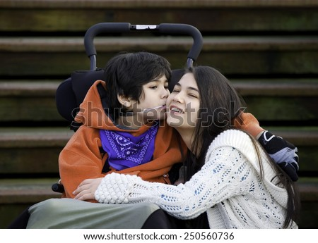 Disabled little boy kissing his big sister on cheek while seated in wheelchair Stock photo ©