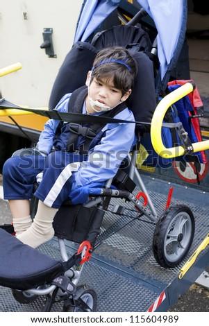 Disabled little boy on school bus wheelchair lift