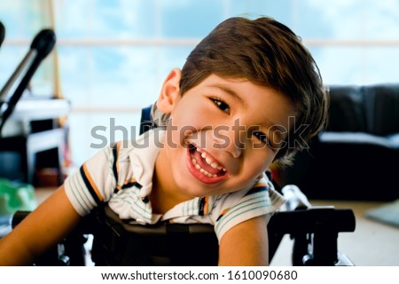Disabled little boy standing in walker smiling and happily looking at camera with bright blue sky and clouds in the background window Stock photo ©