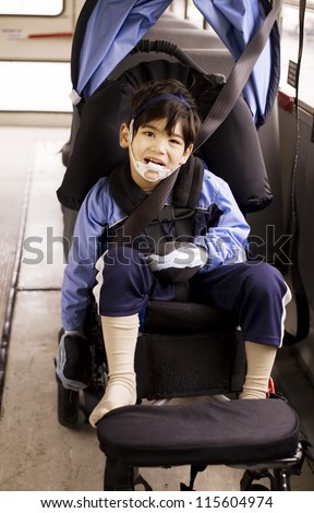 Disabled little preschool boy in wheelchair on bus. Child has cerebral palsy.