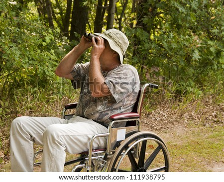 disabled man in a wheelchair watching for birds with a pair of binoculars