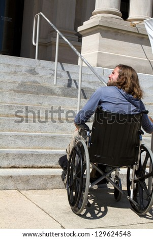 Disabled man in wheelchair looks for a ramp to gain access to a public building entrance.