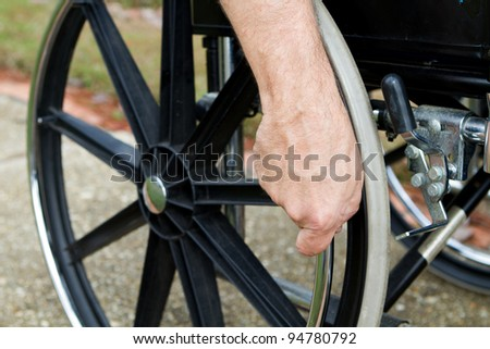 Disabled man's hand grips the push rim on his wheelchair.