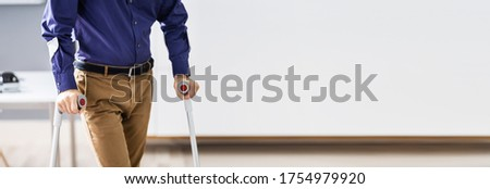 Disabled Man Walking With Crutches. Handicapped Worker At Workplace  Stock photo ©