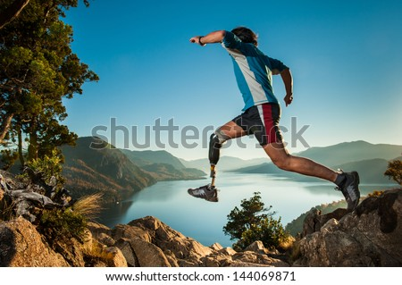 Disabled man with prosthetic leg, jumping in Patagonia. Foto stock ©
