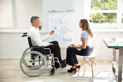 Disabled Matured Businessman Showing Diagram While Giving Presentation To His Colleague In Office