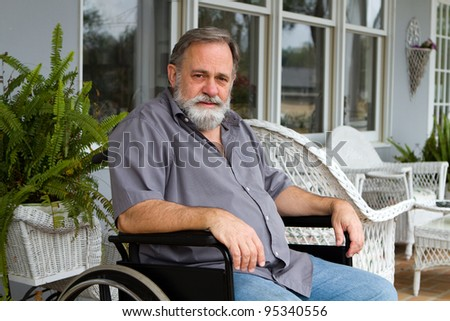 Disabled paraplegic man sits depressed in his wheelchair posing on the porch.