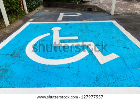 Disabled parking permit sign painted on car parking