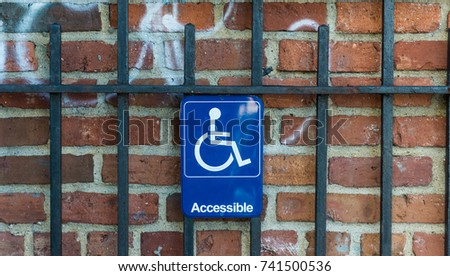 disabled parking symbol on metal gate and brick wall background #741500536