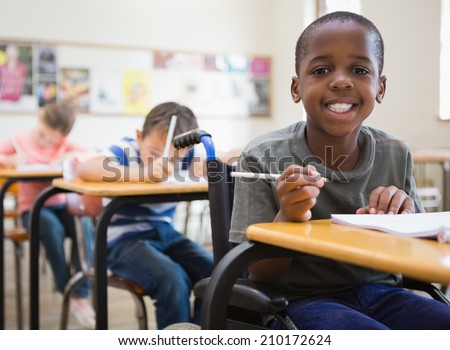 Disabled pupil smiling at camera in classroom at the elementary school #210172624
