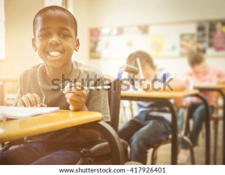 Disabled pupil smiling at camera in classroom at the elementary school #417926401
