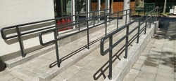 Disabled ramps next to the building's entrance. New school equipped according to modern standards. Accessible environment. Devices for people with disabilities. Metal railings and side slopes