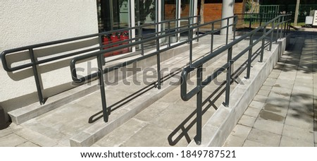 Disabled ramps next to the building's entrance. New school equipped according to modern standards. Accessible environment. Devices for people with disabilities. Metal railings and side slopes Foto stock ©
