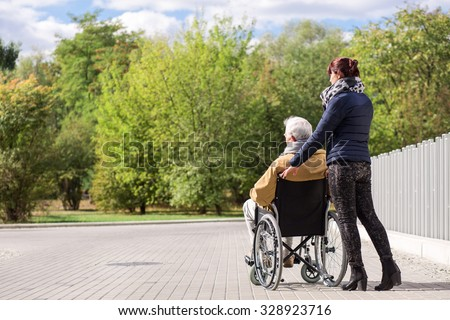 Disabled senior man and assistant in the park