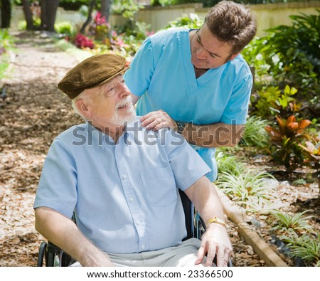 Disabled senior man in the garden with his male nurse.