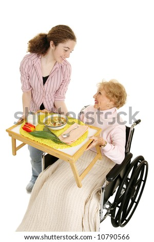 Disabled senior receives a home meal delivery from friendly teen volunteer.  Vertical view isolated on white.
