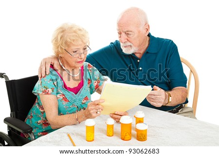 Disabled senior woman and her husband go over their medical and prescription drug bills.  Isolated on white.