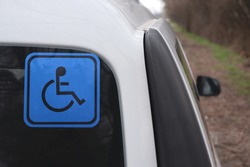 Disabled sign on a car. Blue sticker on the rear window of a white car.