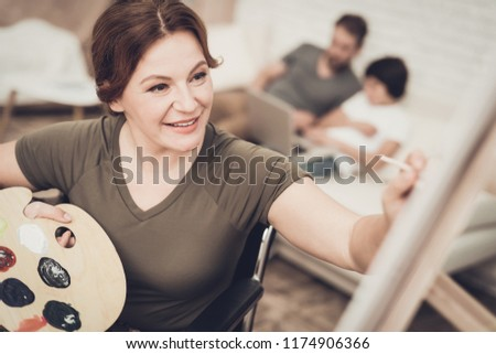 Disabled Soldier In Wheelchair Draws A Picture. After War Concept. Camouflage Uniform. Paralyzed Woman With Tassel. Home Leisure. Return From Army. Family Background. Husband And Son.