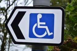 Disabled street sign with direction, wheelchair users