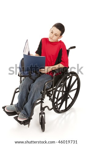 stock photo : Disabled teen boy doing homework in his wheelchair.