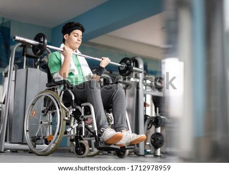 Disabled teenage boy in wheelchair having gym training ストックフォト ©