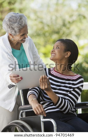 Disabled Woman in a wheelchair sharing a Digital Tablet with her mother
