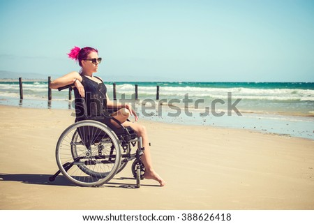 Disabled woman in the wheelchair at the beach. Cross-processed and color-toned image.