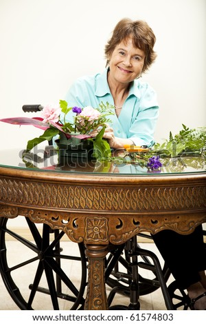 Disabled woman in wheelchair arranging a bouquet of flowers.