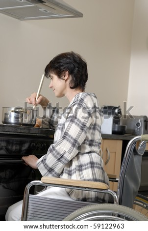 Disabled woman in wheelchair preparing dinner