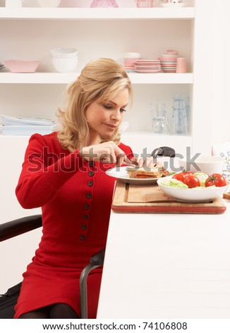 Disabled Woman Making Sandwich In Kitchen