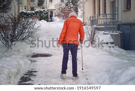 Disabled woman walks with stick after snowfall. Lame woman, disability and injury concept. Old woman with cane walking along slippery sidewalk in winter. Grandma with stick walking along snowy street Photo stock ©