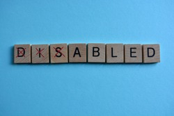Disabled. Word in 3D wooden alphabet letters with the letters dis crossed out, leaving the word Abled.