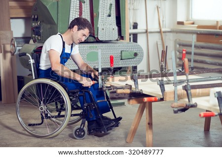 disabled worker in wheelchair in a carpenter\'s workshop