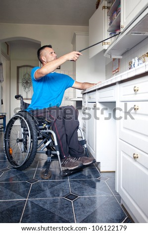 Disabled young man in wheelchair for reaching dishes from cupboard