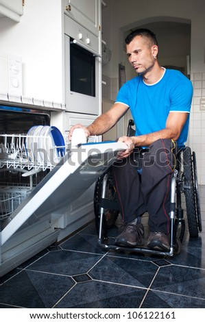 Disabled young man in wheelchair gives the dishwasher on