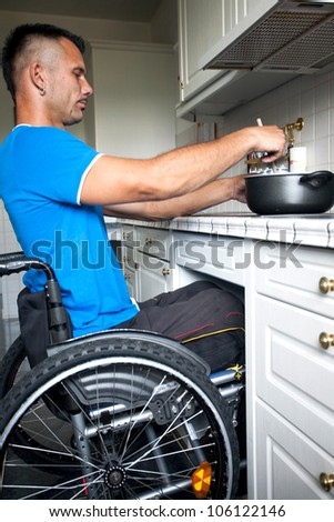 Disabled young man in wheelchair is cooking a meal in the kitchen
