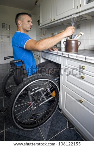 Disabled young man in wheelchair preparing dinner in the kitchen