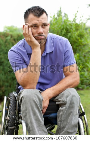disabled young man in wheelchair with a pensive facial expression