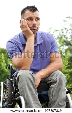 disabled young man in wheelchair with a pensive facial expression, sad look