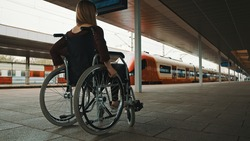 Disabled young woman waiting for a train in the wheelchair. High quality photo