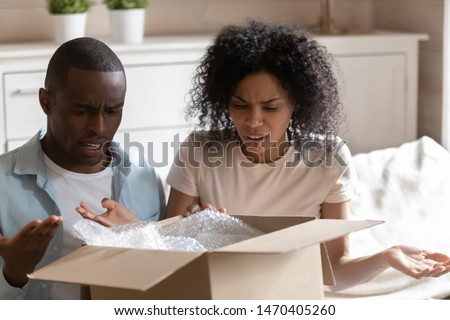 Disappointed angry millennial african american married spouse sitting at home, unpacking cardboard box, received damaged item or unwanted stuff. Annoyed customers dissatisfied by delivery service.
