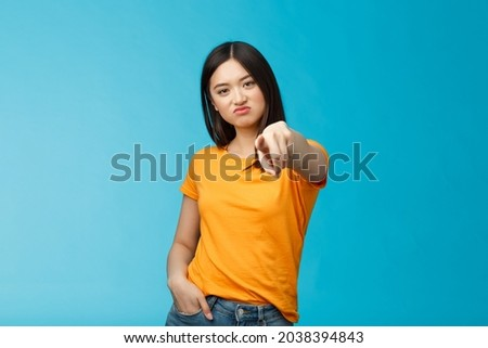Disappointed attractive asian girl frowning, grimasing upset, pointing index finger camera upset unsatisfied, disliking you, accuse someone, blame person, standing displeased blue background Photo stock ©