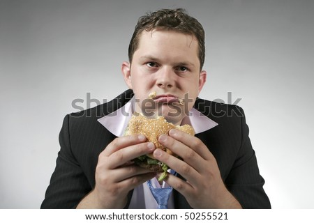 Disappointed businessman eating fast food burger